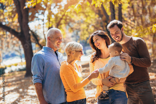 Leinwanddruck Bild Multl generation family in autumn park having fun