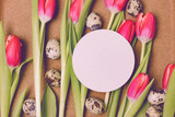 Blank white greeting card on pink tulips and quail eggs. Cork abstract background