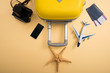 top view of yellow suitcase, plane model, starfish, film camera, smartphone and tickets on beige background