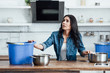 Quadro Confused brunette woman dealing with water damage in kitchen