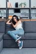Smiling brunette girl in jeans sitting on sofa