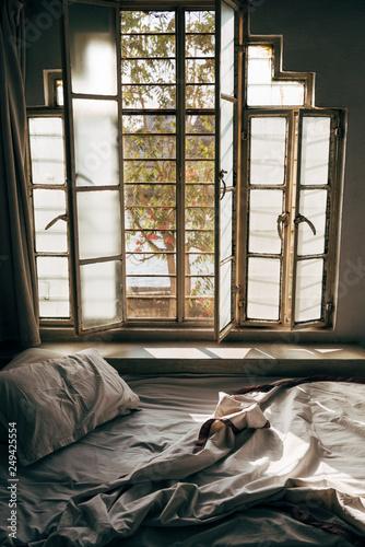 Leinwanddruck Bild Daylight shining through an unmade bed