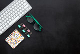 Work desk of manager. Computer keyboard, glasses, stationery, plant on black background top view space for text