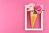 Flower card. Flower frame. Pink roses in an waffle cone  in a white  frame on a  fuchsia background. Flower ice cream.top view,copy space.Mothers Day. International Women's Day.