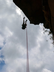 Abseiling a negative sanstone rock wall with blue sky on background - view from bellow © tacio philip