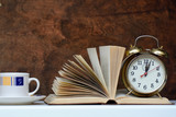 An open book, a cup of coffee and an alarm clock on a dark background