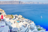 European Destinations. Amazing View of Classic White Houses and Blue Colors of Oia Village Houses And Architecture on Santorini Island in Greece. Sailing Boat in Background.