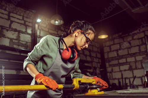 Leinwanddruck Bild Busy and serious craftswoman grinding timbers with special machine. Beautiful woman wearing safety glasses. Concept of joiner's shop and woodworking. Gender equality. Male profession