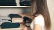 Leinwandbild Motiv Housewife organizing clothes in wardrobe, close up