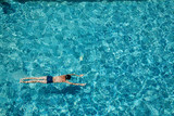 Teen boy swimming underwater in a pool outdoors - 249525703