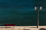 Pier in the sea, red bench and street light in front of blue sea.