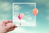 Ręka trzyma błyskawiczne zdjęcie z balonów powietrznych, myśleć poza koncepcją pudełka