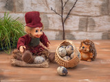 Fabulous picture with small toys. Hedgehog and Lesovik rest in the forest. They carry a large basket of quail eggs.