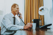 Waist up of businessman sitting at the table and having phone talk