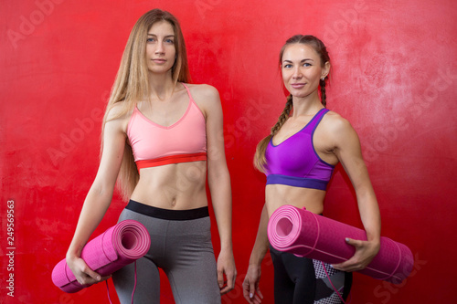 Leinwanddruck Bild Fit women are holding yoga mats in a gym