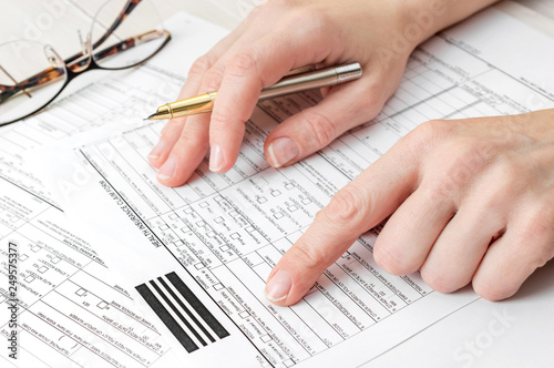 Woman filling health insurance claim form. Close up.