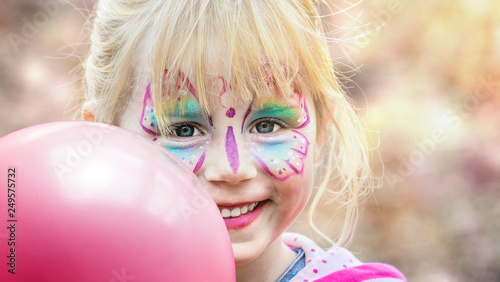 Leinwanddruck Bild Glückliches geschminktes Mädchen beim Kinderkarneval auf einem Freizeitpark mit einem pinken Luftballon