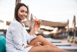 Waist up of positive woman smiling and holding tasty cocktail