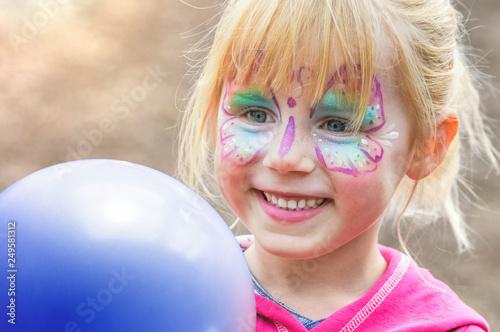Leinwanddruck Bild Kinderschminken beim Kinderkarneval auf einem Freizeitpark mit einem Luftballon