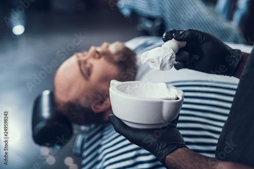 Calm master preparing shaving foam in white bowl