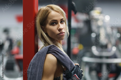 close up portrait of young beautiful woman in fitness gloves with towel over blurred gym interior - 249611367