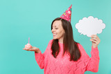 Smiling woman in birthday hat looking on cake with candle, hold empty blank Say cloud, speech bubble for promotional content isolated on blue background. People lifestyle concept. Mock up copy space. - 249650192