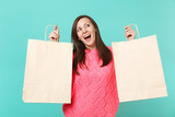 Excited funny young woman in knitted pink sweater looking up, holding empty package bag with purchases after shopping isolated on blue wall background. People lifestyle concept. Mock up copy space. - 249651964