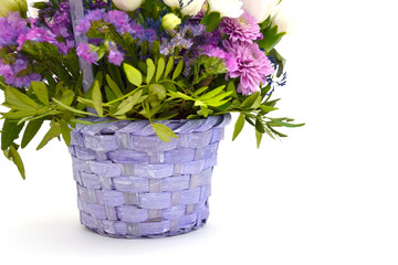 Isolated bouquet of spring flowers in decorative wicker wooden basket of lilac and purple flowers on a white background