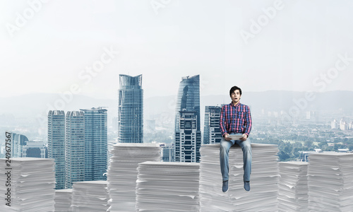 Attractive man sitting on pile of paper documents. - 249677567