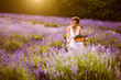 Woman at lavender flower field in summer sunset