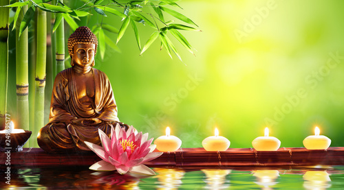 Leinwandbild Motiv Buddha Statue With Candles In Natural Background