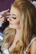 Quadro Visagiste applies makeup for a beautiful blonde girl with wedding hairstyle