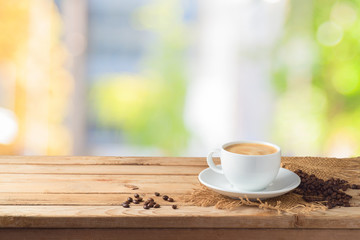 Coffee cup with coffee beans on wooden table over abstract bokeh background with copy space