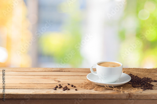 Coffee cup with coffee beans on wooden table over abstract bokeh background with copy space © maglara