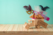 Jewish holiday Purim background with toy truck, carnival mask, noisemaker and hamantaschen cookies on wooden table.