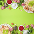 Jewish holiday Passover background with matzo, seder plate and spring flowers.
