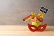 Jewish holiday Purim background with bucket, carnival mask, noisemaker and hamantaschen cookies on wooden table.