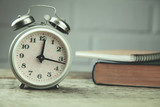 alarm clock and book on the wooden table