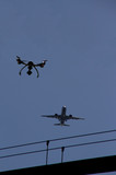Drone in the sky near airport with approaching airplane