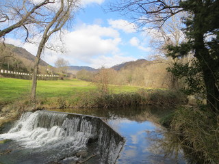 waterfall in a flowing stream with a view of a village and a blue sky