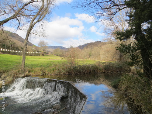 waterfall in a flowing stream with a view of a village and a blue sky - 249733164