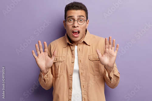 Leinwanddruck Bild Indoor shot of frightened man in spectacles with fearful expression, shows palms, keeps hands in protective gesture, wears casual beige shirt, isolated over purple background. Oh no, stop this