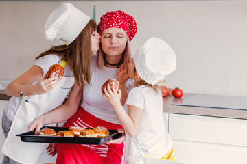 young girls and mother in chef clothes with baked donuts © Simonforstock