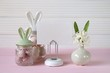 Easter holiday.Spring  Easter Mockup.decorative jar with bunny ears easter eggs, white board, hyacinth flower on a pink table on a white wooden background.Easter mood. Spring mood