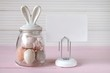 Easter holiday.Spring  Easter Mockup.decorative jar with bunny ears easter eggs, white board  on a pink table on a white wooden background.Easter mood. Spring mood