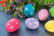 Easter eggs decoration with and flowers on gray wooden table.