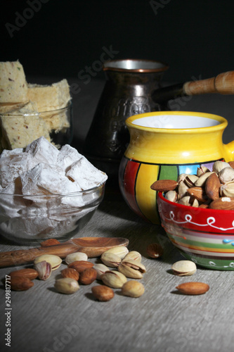 A mug of coffee and different oriental sweets: turkish delight, halva, almond and pistachio © nastyakamysheva