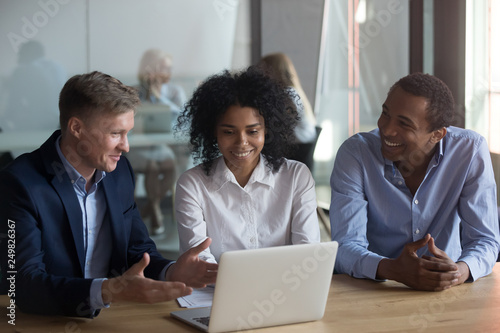 Three workmates sitting at desk working together using laptop