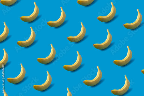 Pattern of yellow bananas on blue background. - 249836301