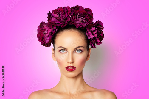 Leinwanddruck Bild Beauty Sexy Model girl with peony flowers wreath. Beautiful brunette young woman perfect make-up, red seductive lips. Trendy makeup, beauty spa skin concept pink background